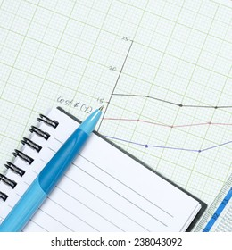 Pen on blank note book with graph paper background.