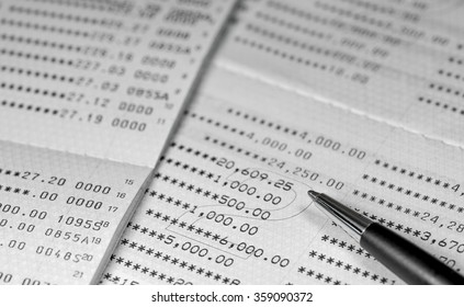 pen on book bank black and white color tone style / calculate investment payment or income / loan and budget monthly spreadsheet background