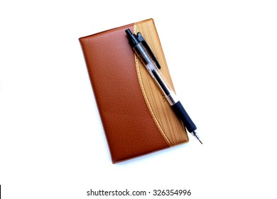 pen is on brown notebook on white background