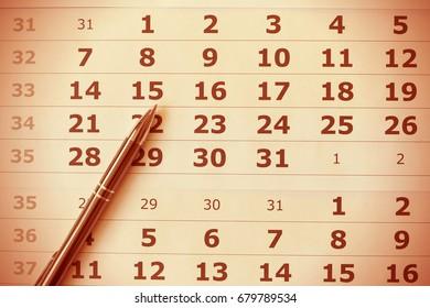 Pen on calendar sheet close up