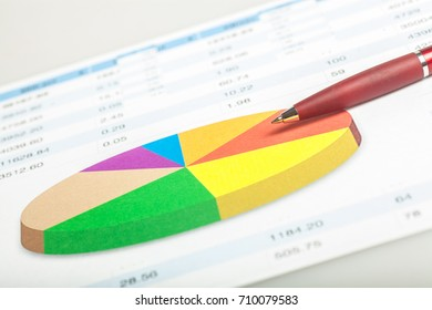 Pen on documents with chart and numbers