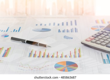 Pen on earnings report with calculator on desk of financial adviser. Concept of invest planning, analyze return on investment.