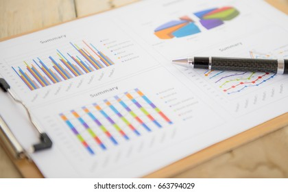 Pen on financial charts and graphs ,Data analyzing from charts and graph to find out the result