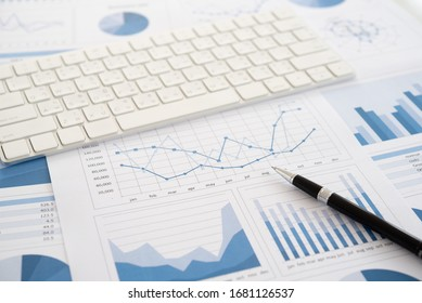 Pen on financial report with keyboard on desk of financial adviser. Concept of invest planning, analyze return on investment.
