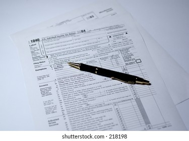 Pen on IRS forms 1040 and 1099. Shallow depth of field, focus on tip of the pen.