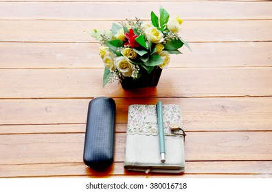 Pen on note book and Spectacles glasses with plastic flower on wooden table