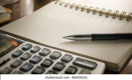 a Pen on a notebook with a Calculator