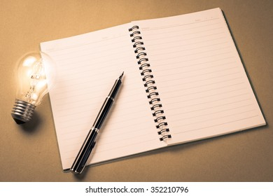 Pen on notebook with glowing light bulb as idea for writing concept