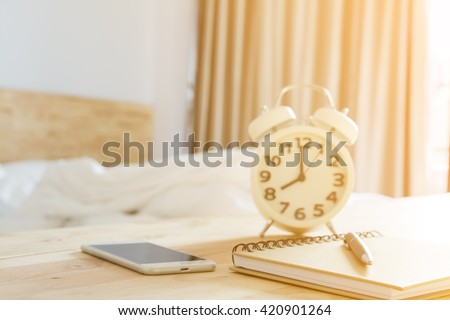 pen on notebook, smartphone alarmclock in bed room with lighting morning time selective focus and blurred background