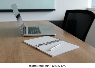 Pen on notepad and laptop and for agenda kept on table in empty corporate conference room. selected focus on pen and notepad.