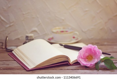 A pen on an open book with a pink rose