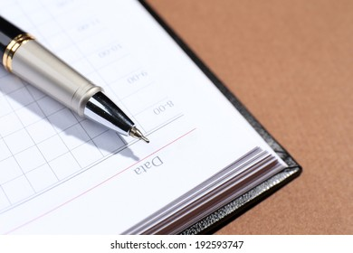Pen on opened book on brown table