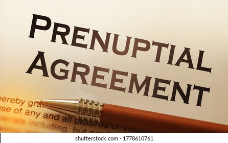 A pen on paper with words prenuptial agreement. Marriage contract concept.