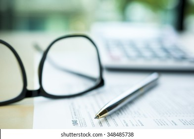 Pen on tax form with blur calculator and eyeglasses background