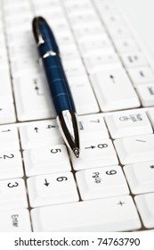Pen on an white keyboard