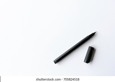 pen on white table with over light in the background