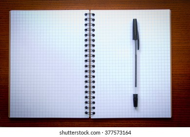 Pen and open Notepad on wooden background