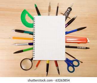 pen, pencil and magnifying glass under checked notebook on wood texture