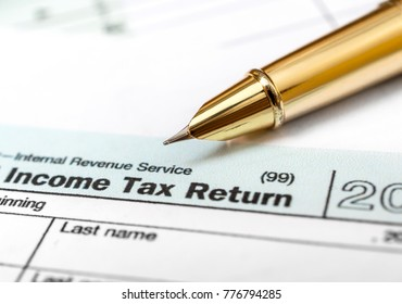 "Pen pointing on word ""tax"" on the tax form. Close up. Business concept."