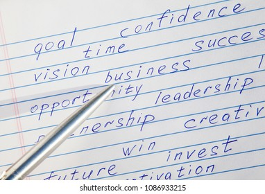 """Pen pointing to the word """"business"""" written among motivational words in a copybook"""