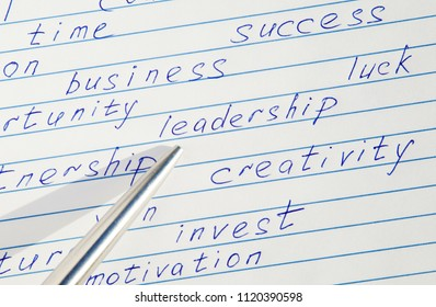 """Pen pointing to the word """"leadership"""" written among motivational words in a copybook"""