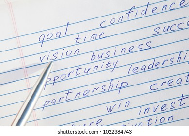 "Pen pointing to the word ""vision"" written among motivational words in a copybook"