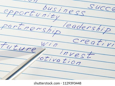 """Pen pointing to the word """"win"""" written among motivational words in a copybook"""
