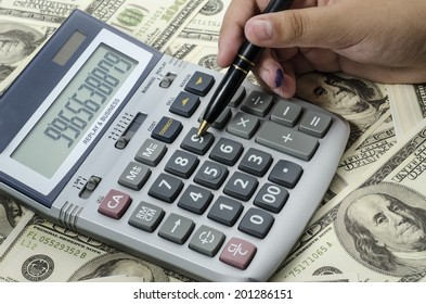 Pen  pressing on a calculator to calculate the financial report