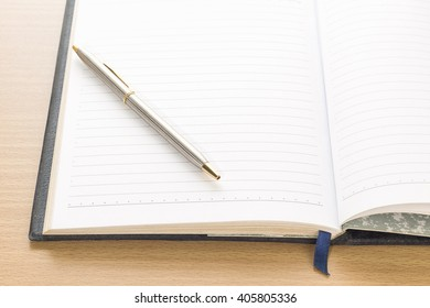 Pen put on notebook open blank page on wood table