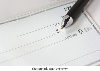A pen resting on a blank check.