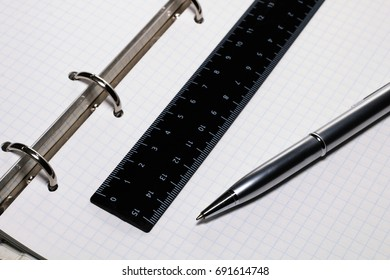 Pen, ruler on a sheet of notebooks in a box
