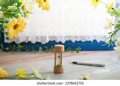 Pen and sandglass on the table.