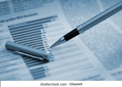 Pen showing diagram on financial report/magazine (blue tone)