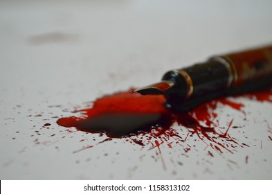 Pen and spilled red ink depicting that a pen is mightier than a sword