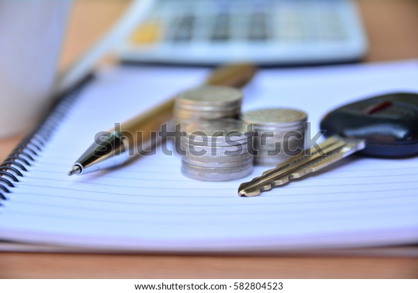 Pen, stack coins, key of car put on note book and calculator for finance and business