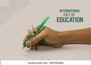 A pen tightly knotted between fingers of a writing hand with a rope. creative concept to illustrate hard study, Perseverance, diligence, persistence etc. idea for International Education Day, writing.