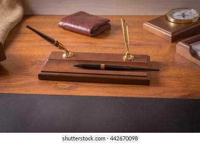 Pen, watch and wallet on a desktop