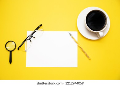 pen white paper magnifier glasses and coffee Cup on yellow background with copy space top view.