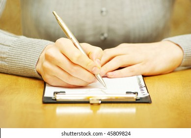 Pen in woman hand isolated on wood background