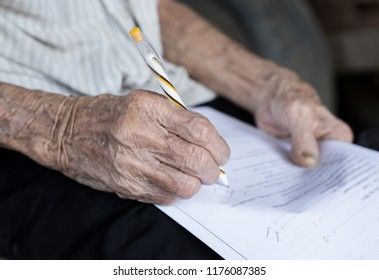 pen writes words on paper sheet, hand of old man