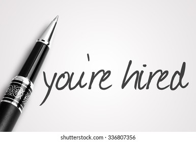 pen writes you're hired on white blank paper.