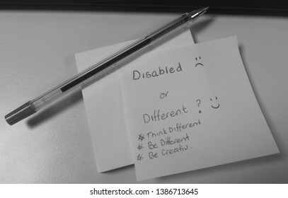 A Pen Written Sticky Note on top of a Sticky Note Pad with Pen Laid over the top describing being disabled or different with hashtags think different be different and be creativ