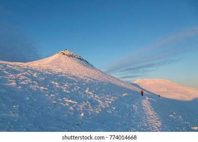 Pen y Fan, Wales, UK: December 11, 2017: A man walks toward the camera in a winter snow scene on Pen y Fan mountain in the Brecon Beacons National Park
