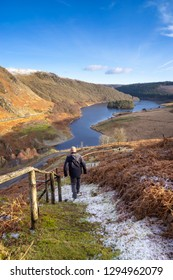 pen y garreg reservoir, Elan Valley Wales. Hiker walking towards lake on a snow covered path looking towards mountains and trees