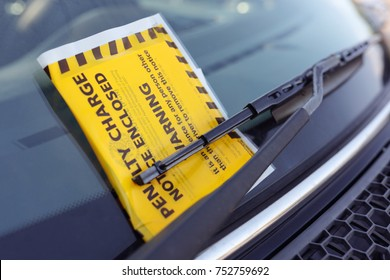 Penalty charge notice parking fine attached to car windscreen