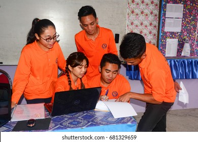 Penampang Sabah Malaysia - Jul 19, 2017: Five students discuss project assignments in class.  Student centered instruction and collaborative learning is the aim of 21st century education in Malaysia.