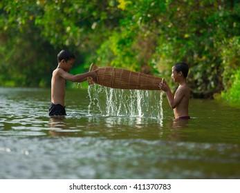 Penampang,Sabah,Malaysia-March 23,2016;Undentified boy of Kadazan Dusun in the Babagon river. They saw the fish trap(Bubuh).