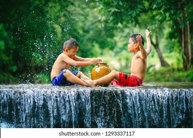 Penampang,Sabah,Malaysia-Oct 29,2016:Kadazan-Dusun kids play the water in the river at Penampang,Sabah Borneo,Malaysia. Kadazan-Dusun are traditional farmers cultivating paddy rice & ravine fishing.