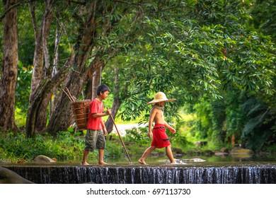 Penampang,Sabah-Oct 29,2016:Kadazandusun kids cross the river with carry basket at Penampang,Sabah,Malaysia.Kadazan is one of the famous cultures in Sabah.38% of people in Sabah are Kadazandusun.