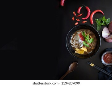 Penang Laksa Noodle Soup flat lay with ingredients on a black table. Malaysian Assam Laksa on a dark wooden table with ingredients spread on the table. Malaysian Penang Laksa with copy space.
